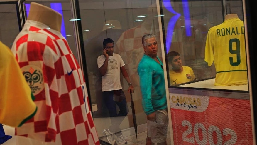 National soccer team jerseys from previous Soccer World Cup tournaments are exhibited on a shopping mall in Salvador, Brazil, Thursday, June 19, 2014. (AP Photo/Bernat Armangue)
