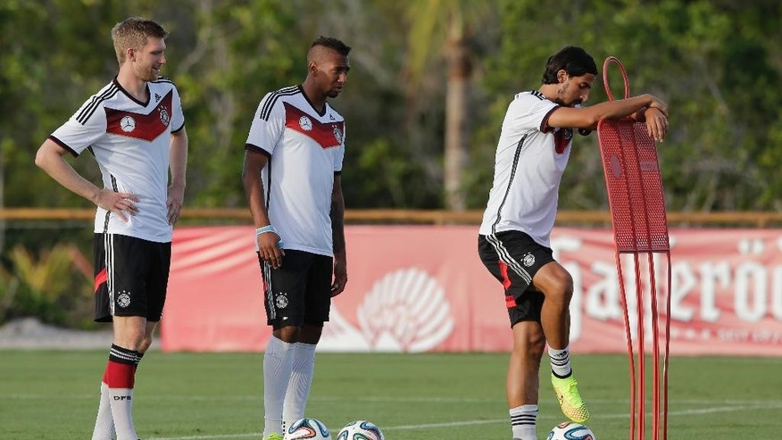 Germany's national soccer players Per Mertesacker, from left, Jerome Boateng and Sami Khedira attend a training session in Santo Andre near Porto Seguro, Brazil, Wednesday, June 18, 2014. Germany play in group G of the 2014 soccer World Cup. (AP Photo/Matthias Schrader)
