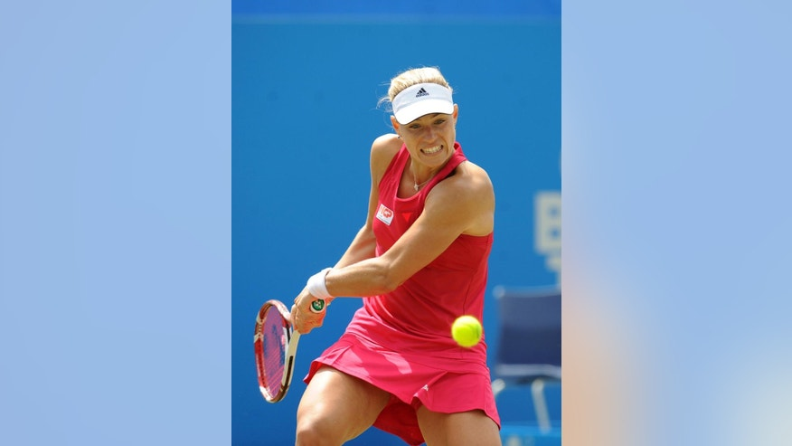 Germany's Angelique Kerber plays a return to Denmark's Caroline Wozniacki during their semifinal match at the Aegon International tennis tournament at Devonshire Park, Eastbourne, southern England, Friday June 20, 2014. (AP Photo/PA, Clive Gee) UNITED KINGDOM OUT  NO SALES  NO ARCHIVE