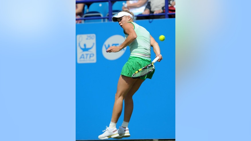 Denmark's Caroline Wozniacki plays a point from behind her back to Germany's Angelique Kerber during their semifinal match at the Aegon International tennis tournament at Devonshire Park, Eastbourne, southern England, Friday June 20, 2014. (AP Photo/PA, Clive Gee) UNITED KINGDOM OUT  NO SALES  NO ARCHIVE