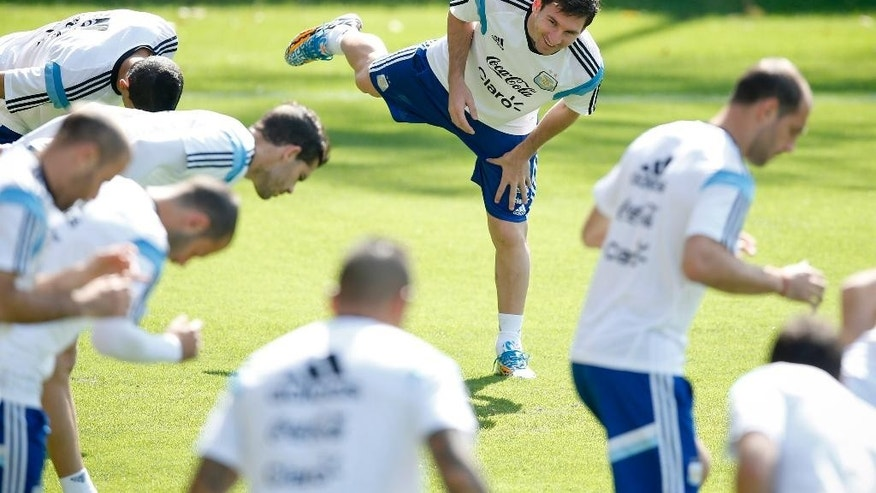 Argentina's Lionel Messi, center, warms up with teammates during a training session in Vespasiano, near Belo Horizonte, Brazil, Friday, June 20, 2014.  Argentina plays in group F of the 2014 soccer World Cup. (AP Photo/Victor R. Caivano)