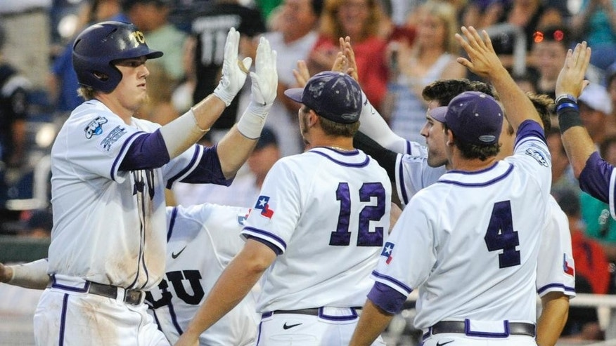 TCU's Kevin Cron, left, celebrates at the dugout with teammates Riley Ferrell (12) and Connor Castellano (4) after he hit a solo home run against Mississippi in the fifth inning of an NCAA baseball College World Series elimination game in Omaha, Neb., Thursday, June 19, 2014. (AP Photo/Eric Francis)