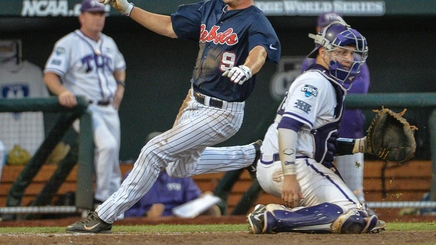 Mississippi's Auston Bousfield (9) runs past TCU catcher Kyle Bacak (6) on his way to score on a single by Sikes Orvis in the fifth inning of an NCAA baseball College World Series elimination game in Omaha, Neb., Thursday, June 19, 2014. (AP Photo/Ted Kirk)