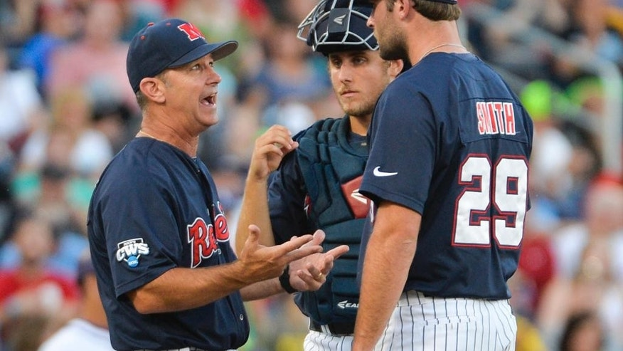 Mississippi coach Mike Bianco, left, talks to pitcher Sam Smith (29) and catcher Austin Knight, center, in the fourth inning of an NCAA baseball College World Series elimination game against TCU in Omaha, Neb., Thursday, June 19, 2014. (AP Photo/Ted Kirk)