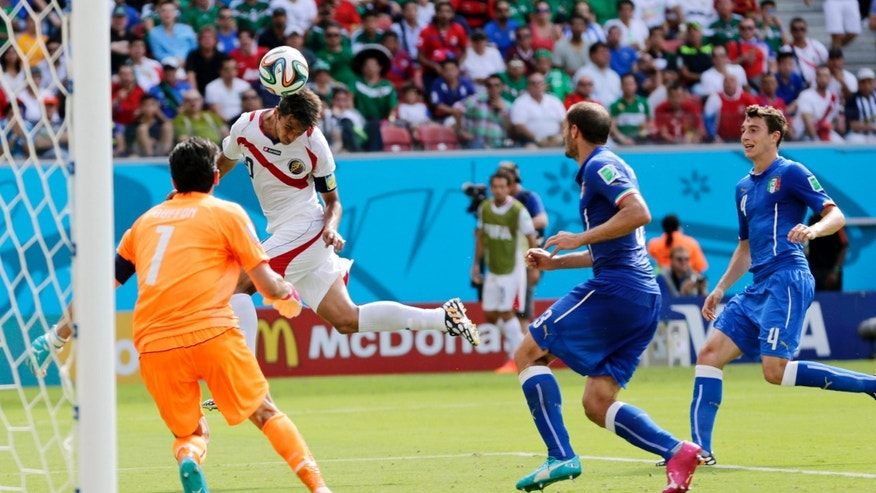 Costa Rica's Bryan Ruiz heads the ball to score his side's first goal over Italy's goalkeeper Gianluigi Buffon during the group D World Cup soccer match between Italy and Costa Rica at the Arena Pernambuco in Recife, Brazil, Friday, June 20, 2014.(AP Photo/Petr David Josek)