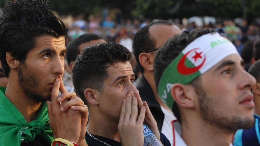 In this photo dated Tuesday, June 17, 2014, an Algerian soccer fans react while watching his team's World Cup soccer match with Belgium on a large screen set up in Algiers Zocalo June 17, 2014. Belgium defeated Algeria 2-1. (AP Photo/Sidali Djarboub)