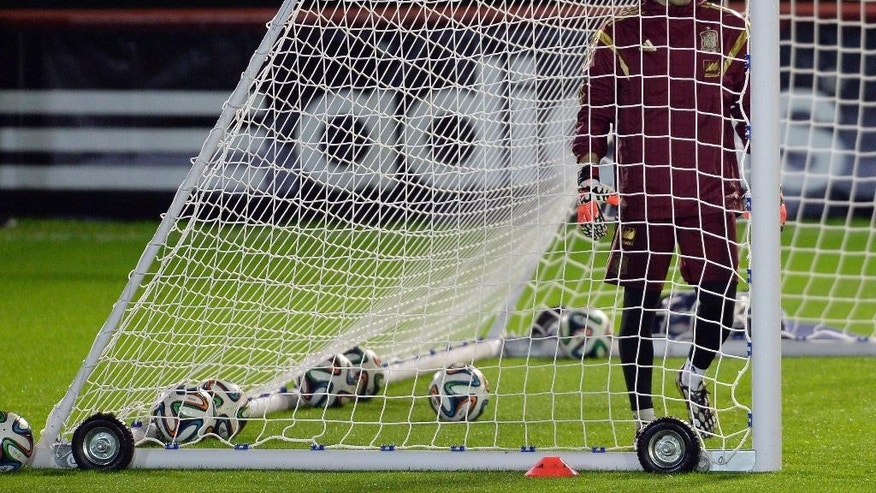Spain's goalkeeper Iker Casillas stands surrounded by balls inside the goal during a training session at the Atletico Paranaense training center in Curitiba, Brazil, Thursday, June 19, 2014.  A 2-0 loss to Chile on Wednesday left Spain without hope of advancing to the second round, becoming the first defending champion to be assured of elimination after just two group games.  Spain will play its last Group A match on Monday against Australia.(AP Photo/Manu Fernandez)