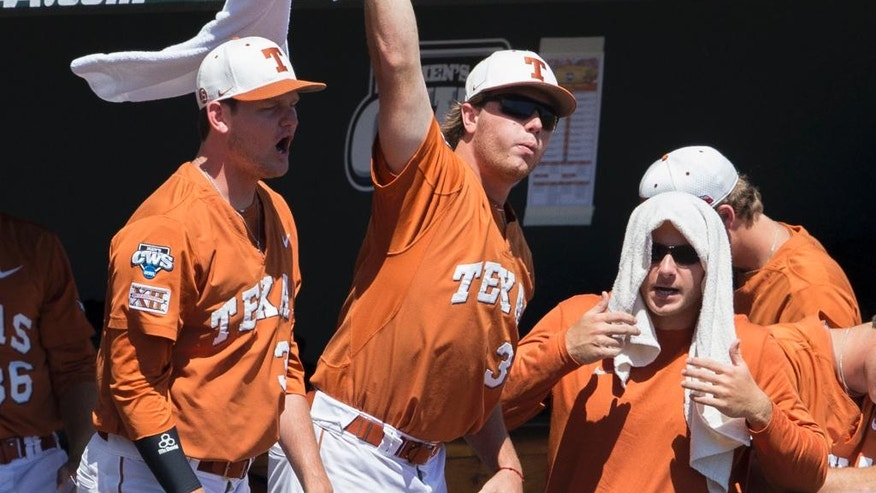 Players in the Texas dugout celebrate after Ben Johnson scored against Vanderbilt in the first inning of an NCAA baseball College World Series game in Omaha, Neb., Friday, June 20, 2014. (AP Photo/Nati Harnik)