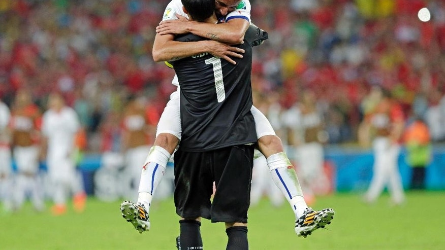 Chile's goalkeeper Claudio Bravo is embraced by Mauricio Isla after the group B World Cup soccer match between Spain and Chile at the Maracana Stadium in Rio de Janeiro, Brazil, Wednesday, June 18, 2014. Defending champion Spain was eliminated from the World Cup after losing to Chile 2-0.  (AP Photo/Bernat Armangue)
