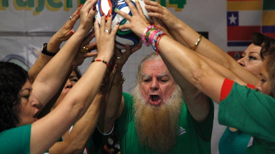 "Mexico City's ""Great Warlock"" Antonio Vazquez, center, and assistants perform a magic ritual using a soccer ball to help Mexico's national soccer team reach the quarter-finals of the Brazil World Cup, in Mexico City, Saturday, June 21, 2014. (AP Photo/Moises Castillo)"