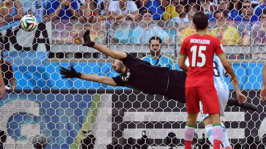 Iran's goalkeeper Alireza Haghighi dives but fails to stop a goal by Argentina's Lionel Messi during the group F World Cup soccer match between Argentina and Iran at the Mineirao Stadium in Belo Horizonte, Brazil, Saturday, June 21, 2014. Argentina defeated Iran 1-0. (AP Photo/Martin Meissner)