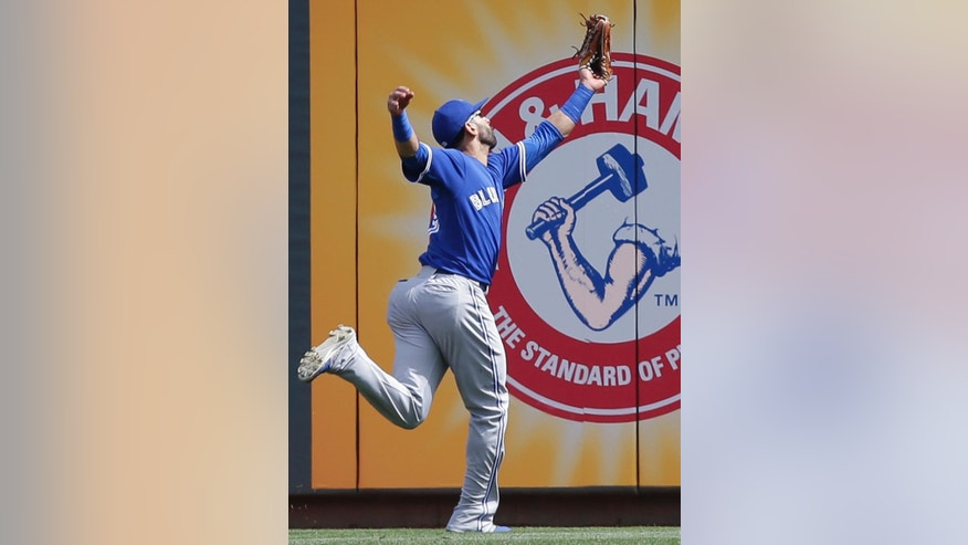 Toronto Blue Jays right fielder Jose Bautista catches a line drive hit by Cincinnati Reds' Todd Frazier in the first inning of a baseball game on Saturday, June 21, 2014, in Cincinnati. (AP Photo/Al Behrman)