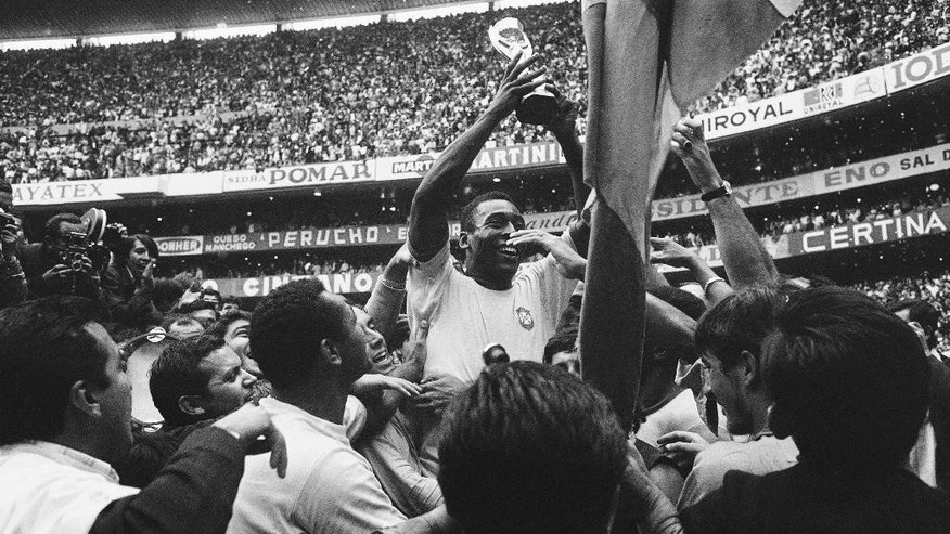 "FILE - The June 21, 1970 file photo shows Brazil's ""King"" Pele as he has a big smile as he holds the Jules Rimet Trophy, following Brazil's victory over Italy in the World Cup final on June 21, 1970 at the Azteca Stadium, Mexico City. Brazil won 4-1 and was given the Jules Rimet Trophy permanently in recognition of its third victory. (AP Photo)"