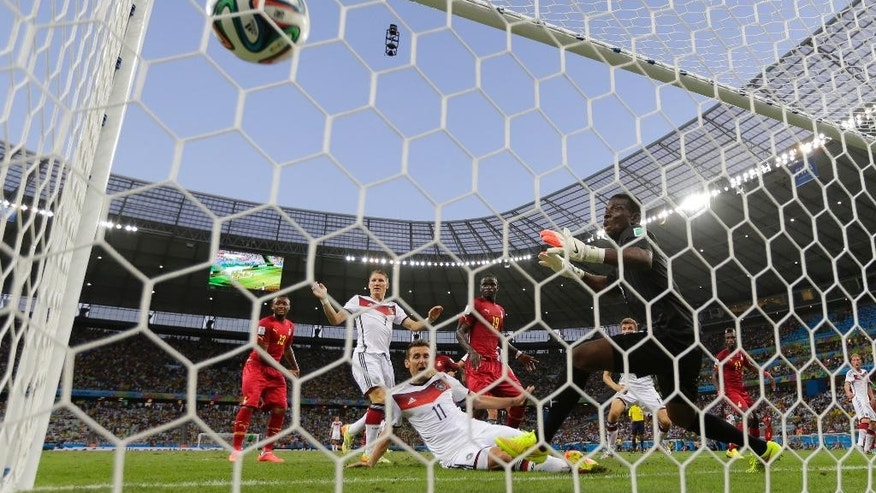 Germany's Miroslav Klose, centre, watches the ball into the net as he scores his side's second goal during the group G World Cup soccer match between Germany and Ghana at the Arena Castelao in Fortaleza, Brazil, Saturday, June 21, 2014. (AP Photo/Frank Augstein)