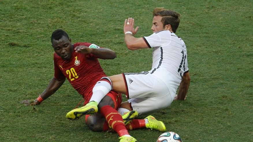 Ghana's Kwadwo Asamoah, left, and Germany's Mario Goetze vie for the ball during the group G World Cup soccer match between Germany and Ghana at the Arena Castelao in Fortaleza, Brazil, Saturday, June 21, 2014. (AP Photo/Themba Hadebe)