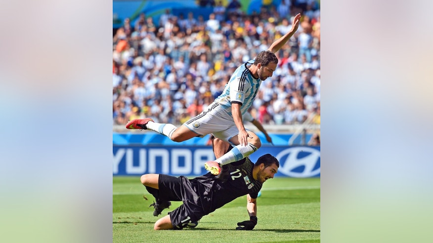 Argentina's Gonzalo Higuain leaps over Iran's goalkeeper Alireza Haghighi after taking a shot on goal during the group F World Cup soccer match between Argentina and Iran at the Mineirao Stadium in Belo Horizonte, Brazil, Saturday, June 21, 2014. (AP Photo/Martin Meissner)