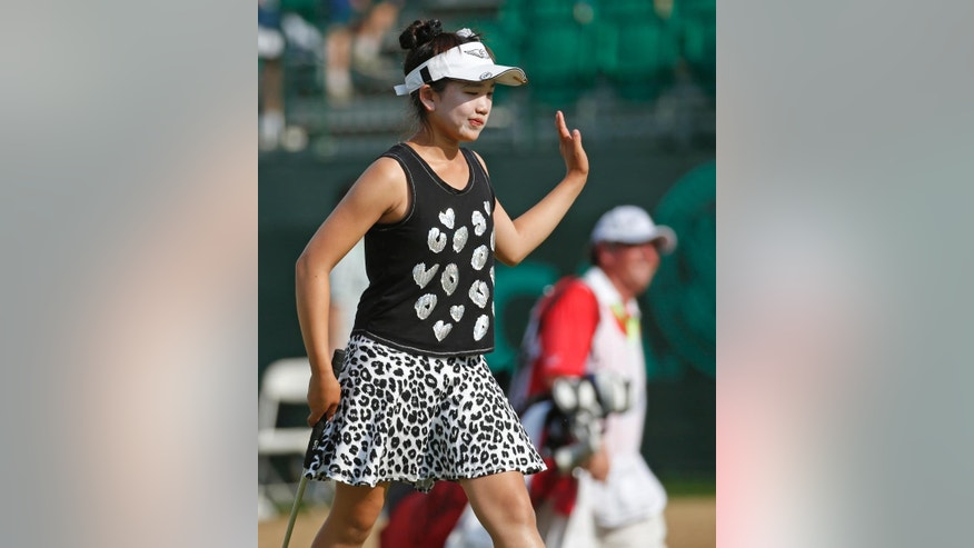Lucy Li waves to fans as she walks to the 18th green during the second round of the U.S. Women's Open golf tournament in Pinehurst, N.C., Friday, June 20, 2014. (AP Photo/John Bazemore)