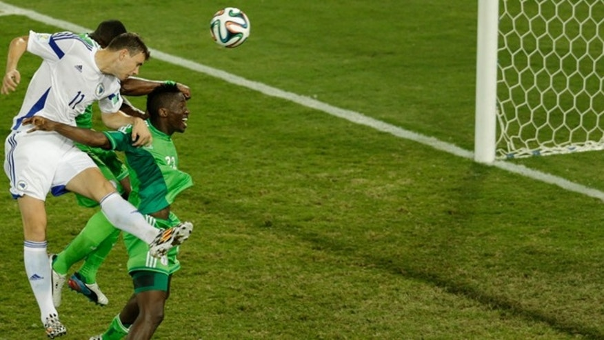 June 21, 2014: Bosnia's Edin Dzeko, left, heads a ball during the group F World Cup soccer match between Nigeria and Bosnia at the Arena Pantanal in Cuiaba, Brazil.