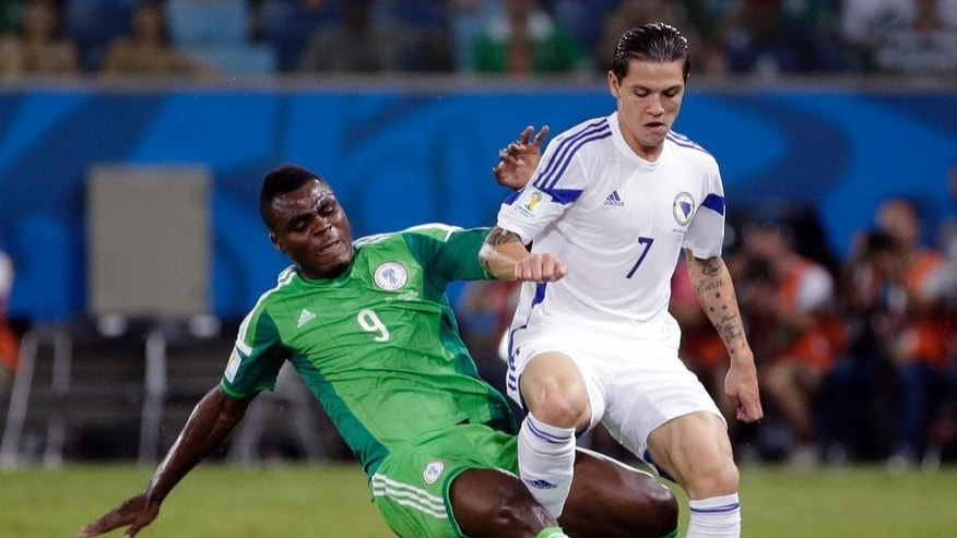 Nigeria's Emmanuel Emenike slides into Bosnia's Muhamed Besic to kick the ball away during the group F World Cup soccer match between Nigeria and Bosnia at the Arena Pantanal in Cuiaba, Brazil, Saturday, June 21, 2014. (AP Photo/Felipe Dana)