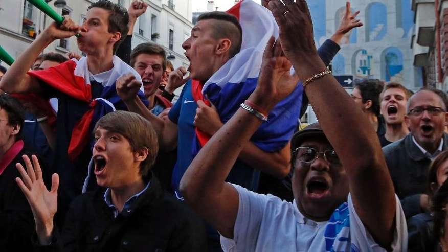 French soccer supporters react after the first goal as they watch a live broadcast of the group E World Cup soccer match between Switzerland and France, in the Metro 14th District bar in Paris, France, Friday, June 20, 2014. The match ended in a 5-2 win for France. (AP Photo/Francois Mori)