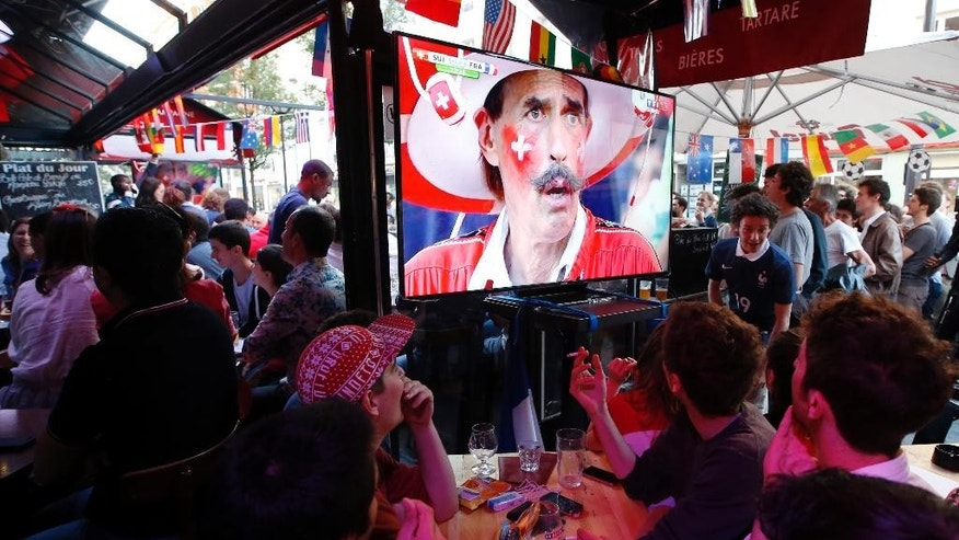 French soccer supporters watch a live broadcast of the group E World Cup soccer match between Switzerland and France, in the Metro14th District bar in Paris, France, Friday, June 20, 2014. The match ended in a 5-2 win for France. (AP Photo/Francois Mori)