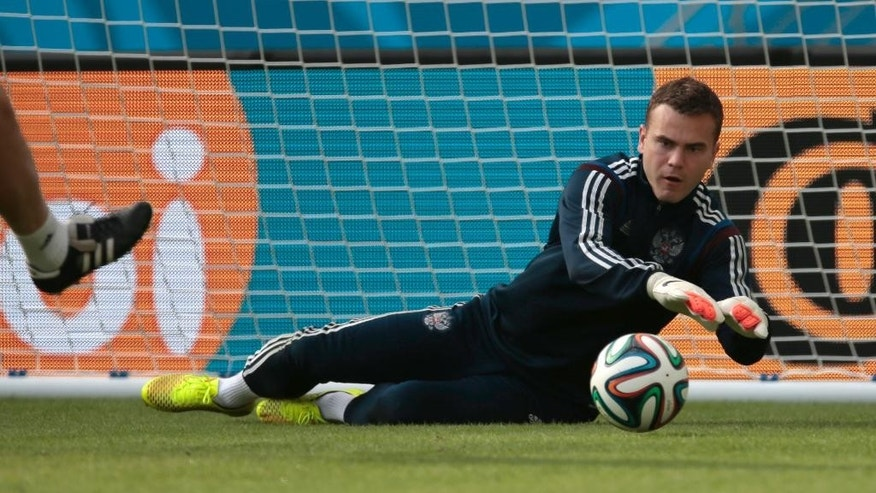 Goalkeeper Igor Akinfeev catches a ball the Russian national soccer team training session at the Maracana stadium in Rio de Janeiro, Brazil, on Saturday, June 21, 2014. Russia will play next game against Belgium in group H of the 2014 soccer World Cup. (AP Photo/Ivan Sekretarev)
