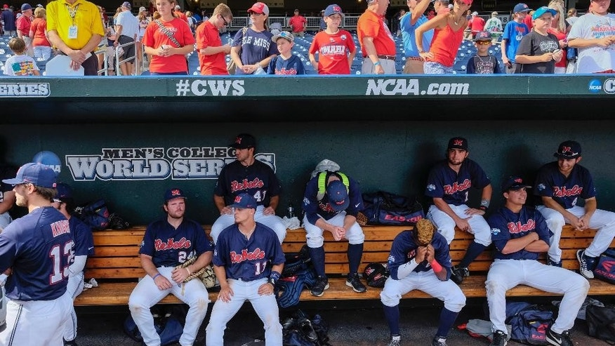 Mississippi players sit dejected in the dugout, as fans looking on overhead, after losing 4-1 to Virginia in an NCAA baseball College World Series game in Omaha, Neb., Saturday, June 21, 2014. Mississippi was eliminated from the tournament while Virginia advances to the championship series. (AP Photo/Eric Francis)