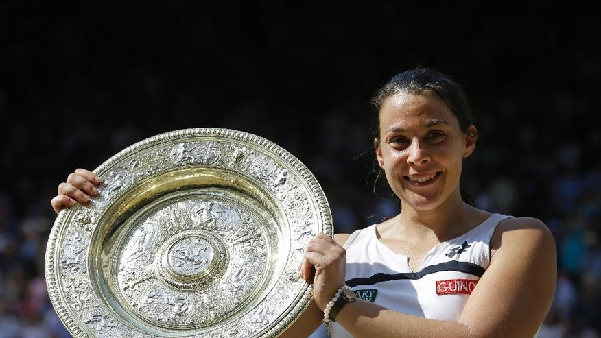 FILE - In this July 6, 2013 file photo, Marion Bartoli, of France, smiles as she holds the trophy after winning the women's singles final against Sabine Lisicki, of Germany, at the All England Lawn Tennis Championships in Wimbledon, London. Bartoli says she has no regrets about retiring shortly after winning Wimbledon a year ago. She also says she logs onto YouTube every couple of days to watch her last-point ace that ended the 2013 final at the All England Club. About six weeks after winning her only Grand Slam trophy, Bartoli announced she was quitting the sport at age 28. Bartoli is the first reigning women's champion at Wimbledon since 1997 to decline to try to defend her title. The Championships starts on June 23, 2014. (AP Photo/Anja Niedringhaus, File)