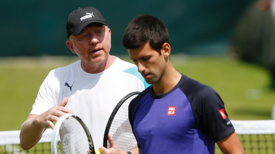 Novak Djokovic of Serbia listens to his coach Boris Becker during a practice session ahead of the All England Lawn Tennis Championships in Wimbledon, London,  Sunday June 22, 2014. (AP Photo/Sang Tan)