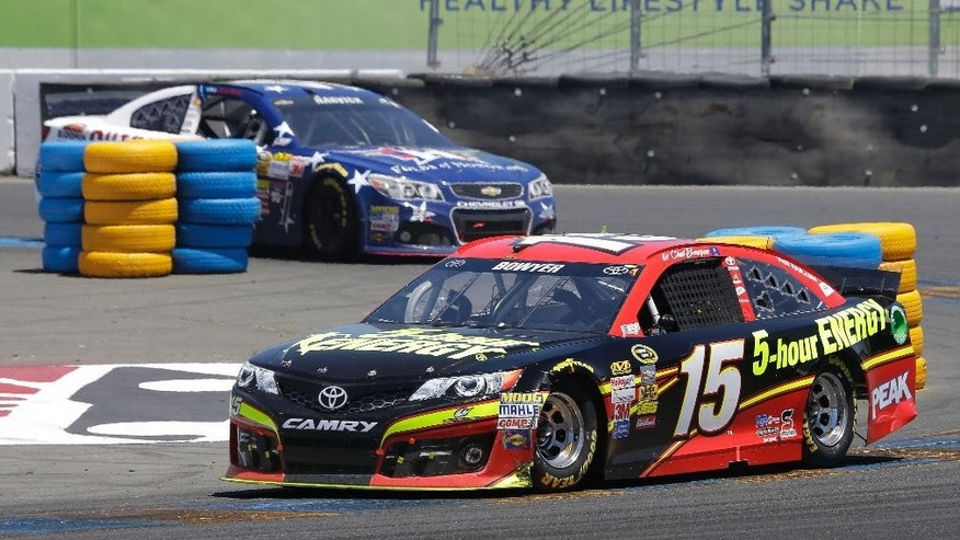 Clint Bowyer (15) leads Kevin Harvick during the NASCAR Sprint Cup Series auto race on Sunday, June 22, 2014, in Sonoma, Calif. (AP Photo/Eric Risberg)