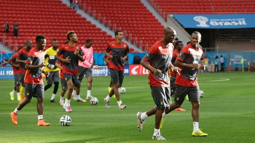 Members of the Cameroon national soccer team jog during an official training session the day before the group A World Cup soccer match between Brazil and Cameroon at the Estadio Nacional in Brasilia, Sunday, June 22, 2014. Cameroon began the tournament with a 1-0 loss to Mexico and a 4-0 defeat to Croatia and it will now face the hosts Brazil. (AP Photo/Andre Penner)