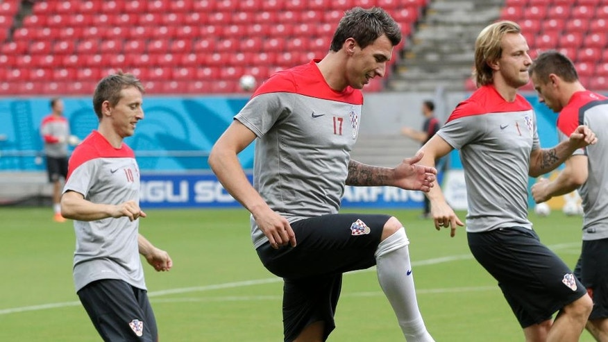 Mario Mandzukic, center, Luka Modric, left, and Ivan Rakitic, right, of Croatia warm up during a training session at the Arena Pernambuco in Recife, Brazil, Sunday, June 22, 2014. Croatia will play Mexico in group A of the 2014 soccer World Cup. (AP Photo/Petr David Josek)