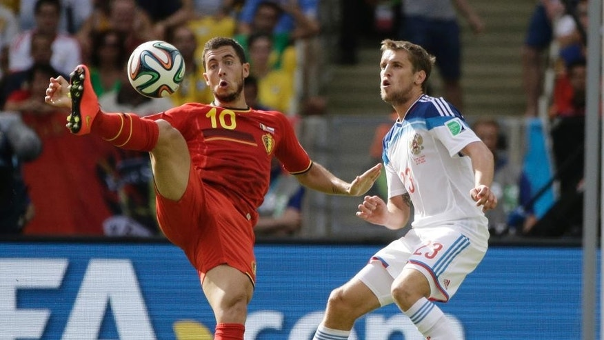 Belgium's Eden Hazard, left, is challenged by Russia's Dmitry Kombarov during the group H World Cup soccer match between Belgium and Russia at the Maracana Stadium in Rio de Janeiro, Brazil, Sunday, June 22, 2014. (AP Photo/Christophe Ena)