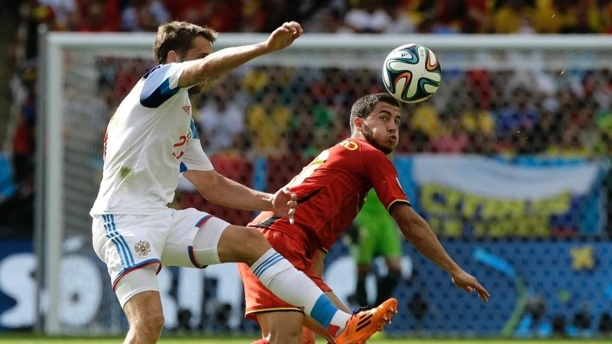 Belgium's Eden Hazard, right, and Russia's Dmitry Kombarov vie for the ball during the group H World Cup soccer match between Belgium and Russia at the Maracana Stadium in Rio de Janeiro, Brazil, Sunday, June 22, 2014. (AP Photo/Christophe Ena)