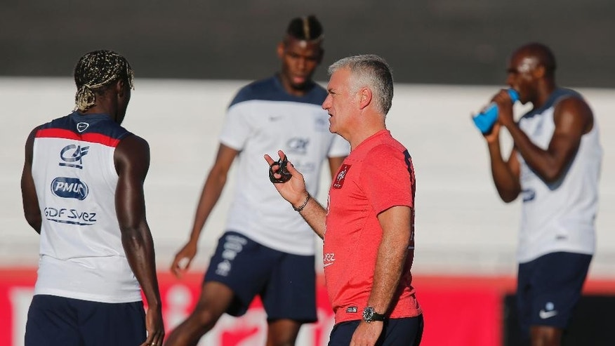 France's head coach Didier Deschamps talks to his layers during a during a training session at the Santa Cruz stadium, in Ribeirao Preto, Brazil, Saturday, June 21, 2014. France faces Ecuador, Switzerland and Honduras in group E of the World Cup. Having captured people's attention at the soccer World Cup with some scintillating attacking football, France's players are now in unknown territory after raising expectations back home, having routed Switzerland and Honduras. (AP Photo/David Vincent)