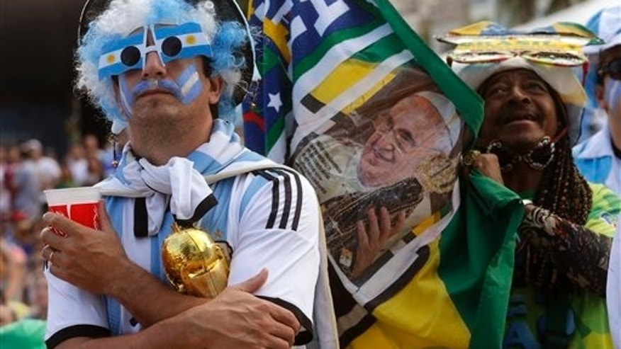 An Argentina soccer fan watches his team's World Cup match with Iran as another fan holds up a photo of Pope Francis inside the FIFA Fan Fest area on Copacabana beach, in Rio de Janeiro, Brazil, Saturday, June 21, 2014. Argentina won 1-0. (AP Photo/Silvia Izquierdo)