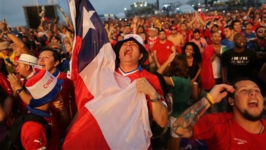 Soccer fans celebrate as they watch a live broadcast of Chile's Charles Aranguiz scoring his side's second goal against Spain, inside the FIFA Fan Fest area on Copacabana beach, in Rio de Janeiro, Brazil, Wednesday, June 18, 2014. Chile defeated Spain 2-0 in their group B World Cup match. (AP Photo/Leo Correa)
