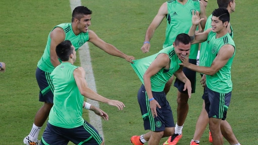 Players of Mexico joke around during a training session at the Arena Pernambuco in Recife, Brazil, Sunday, June 22, 2014. Mexico will play Croatia in group A match of the 2014 soccer World Cup. (AP Photo/Ricardo Mazalan)