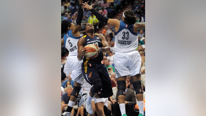 Indiana Fever guard Karima Christmas, center, goes under the arms of Minnesota Lynx defenders guard Tan White, left, and guard Seimone Augustus, right, during the first quarter of a WNBA basketball game Sunday, June 22, 2014, in Minneapolis. (AP Photo/Tom Olmscheid)