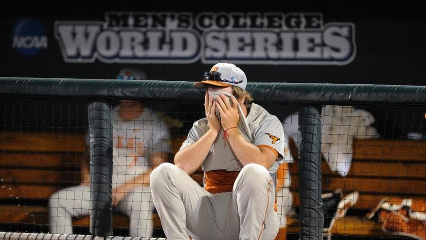 Texas pitcher Dillon Peters covers his face in frontof  the dugout after Texas lost 4-3 to Vanderbilt in 10 innings in an NCAA baseball College World Series elimination game in Omaha, Neb., Saturday, June 21, 2014. Vanderbilt advanced to the championship series. (AP Photo/Eric Francis)