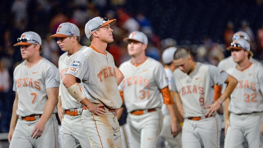 Texas players from left: Weston Hall (7), Parker French (24), Collin Shaw (4), Chad Hollingsworth (31), C.J Hinojosa (9) and Dillon Peters (32) walk after Texas lost 4-3 to Vanderbilt in ten innings in an NCAA baseball College World Series elimination game in Omaha, Neb., Saturday, June 21, 2014. Vanderbilt advances to the championship series.  (AP Photo/Ted Kirk)