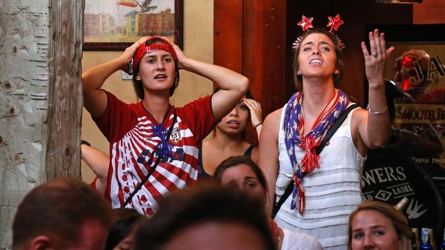 U.S. soccer fans at The Claddagh Irish Pub in Pittsburgh react as Portugal scores to tie the score at 2-2 with less than one minute remaining during a World Cup soccer match against the United States in Brazil Sunday, June 22, 2014. (AP Photo/Gene J. Puskar)