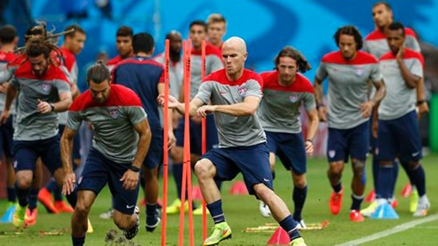 United States' Michael Bradley, center left, runs through obstacles with teammates during a training session at the Arena da Amazonia in Manaus, Brazil, Saturday, June 21, 2014. The U.S. will play Portugal in group G of the 2014 soccer World Cup on June 22. (AP Photo/Paulo Duarte)