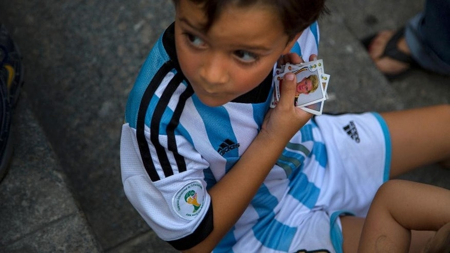 A child wearing the team jersey of Argentina holds photos of soccer players he needs to get, to complete his World Cup sticker album, at a meeting of collectors in Caracas, Venezuela, Saturday, June 21, 2014.  While soccer has long taken a backseat to baseball and even basketball in Venezuela, the ritual of sicker collection still sparks a frenzy. Politicians, TV personalities, and professional collectors can all be found at ad-hoc trading centers, searching for the more than 600 stickers that constitute a complete 2014 collection. (AP Photo/Ramon Espinosa)