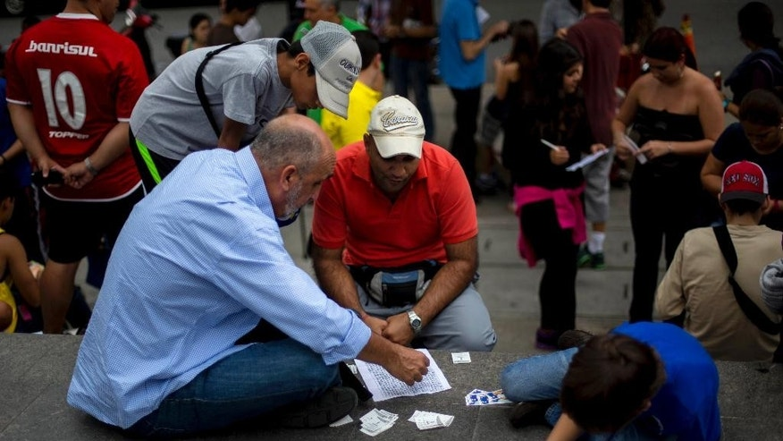 People exchange stickers of soccer players to complete their World Cup sticker albums at a meeting of collectors in Caracas, Venezuela, Saturday, June 21, 2014. Adults and children alike are spilling into plazas around the country to swap and buy business card-sized stickers with the faces of players and photos of Brazilian stadiums. (AP Photo/Ramon Espinosa)