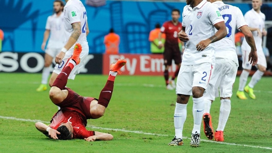 Portugal's Cristiano Ronald, lower left, takes a tumble during the group G World Cup soccer match between the USA and Portugal at the Arena da Amazonia in Manaus, Brazil, Sunday, June 22, 2014. (AP Photo/Paulo Duarte)