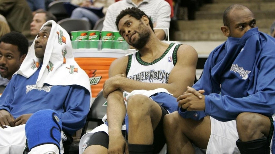 FILE - In this Oct. 27, 2004 file photo, Minnesota Timberwolves' Michael Olowokandi, center, sits on the bench flanked by Anthony Goldwire, left, and Trenton Hassell during the fourth quarter of a basketball game against the Milwaukee Bucks, in Minneapolis. For every Hall of Fame-level big man like Shaquille O'Neal, David Robinson, Tim Duncan and Hakeem Olajuwon, there's a Pervis Ellison, Michael Olowokandi, Kwame Brown and Greg Oden to serve as a cautionary tale. (AP Photo/Ann Heisenfelt, File)