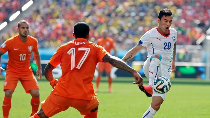Chile's Charles Aranguiz stops a pass in front of Netherlands' Jeremain Lens during the group B World Cup soccer match between the Netherlands and Chile at the Itaquerao Stadium in Sao Paulo, Brazil, Monday, June 23, 2014. (AP Photo/Felipe Dana)