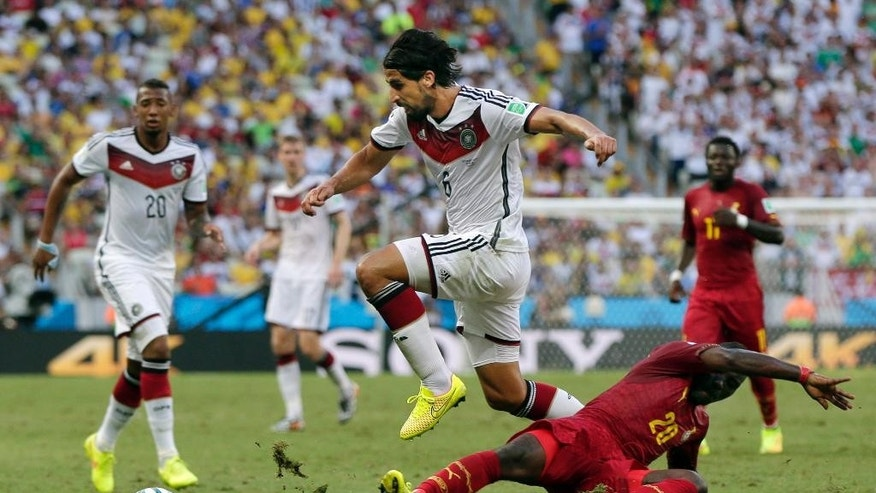 Germany's Sami Khedira, center, jumps over Ghana's Kwadwo Asamoah, right, to attack with the ball during the group G World Cup soccer match between Germany and Ghana at the Arena Castelao in Fortaleza, Brazil, Saturday, June 21, 2014. (AP Photo/Marcio Jose Sanchez)
