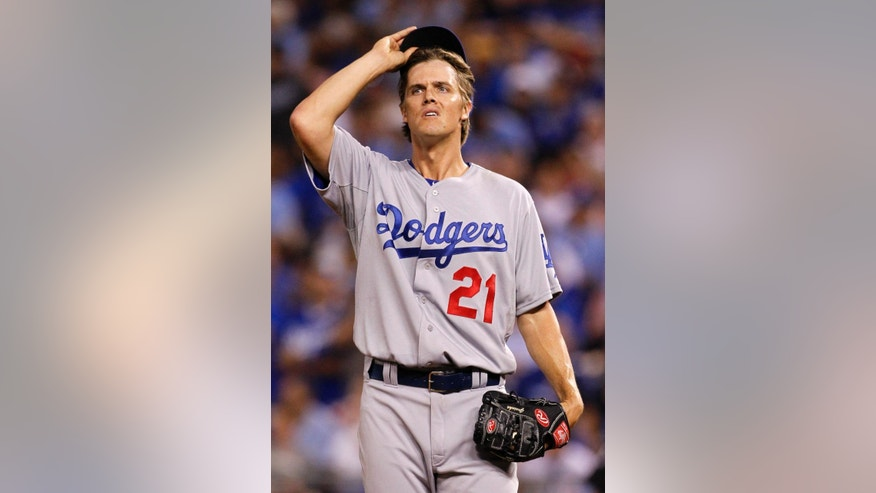 Los Angeles Dodgers pitcher Zack Greinke reacts after an RBI triple by Kansas City Royals' Alcides Escobar in the sixth inning of a baseball game at Kauffman Stadium in Kansas City, Mo., Monday, June 23, 2014.  (AP Photo/Colin E. Braley)